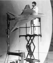 Scale model of fighter aircraft being mounted inside test section of large wind tunnel