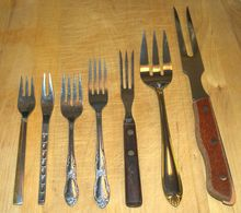 Assorted forks. From left to right: dessert fork, relish fork, salad fork, dinner fork, cold cuts fork, serving fork, carving fork.