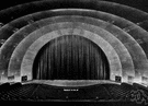 apron - the part of a modern theater stage between the curtain and the orchestra (i.e., in front of the curtain)