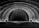 proscenium - the part of a modern theater stage between the curtain and the orchestra (i.e., in front of the curtain)